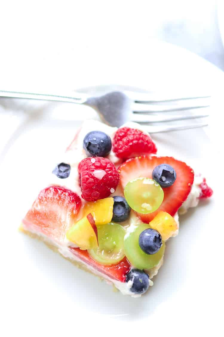 overhead shot of a square slice of vegan fruit pizza on a white plate with fork beside