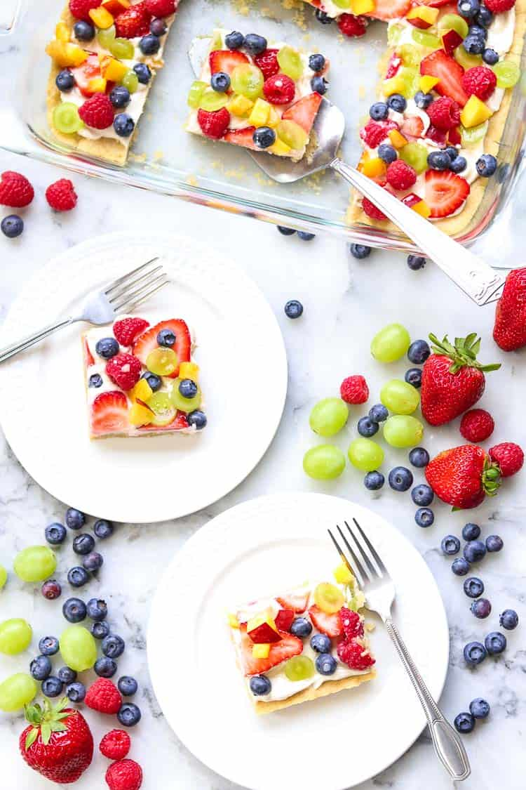 wide overhead shot of fruit pizza in pan and on white plates with strawberries, raspberries, grapes, and blueberries all around