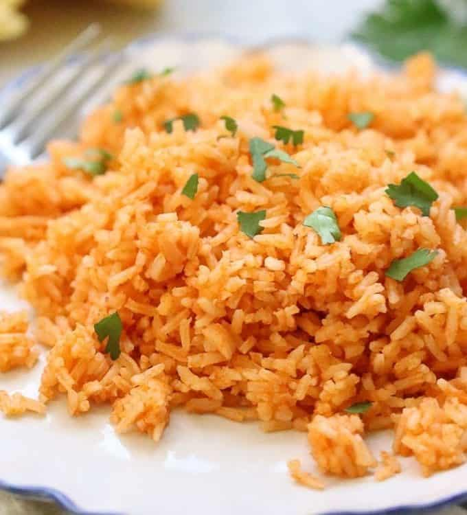 fluffy vegan Mexican rice on a plate with cilantro garnish