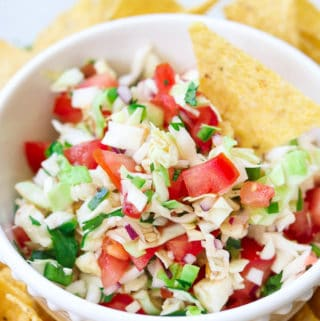 overhead closeup shot of cabbage salsa in a white bowl with a tortilla chip in it