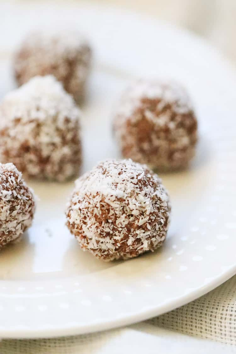 side overhead shot of vegan coconut balls placed on a white plate
