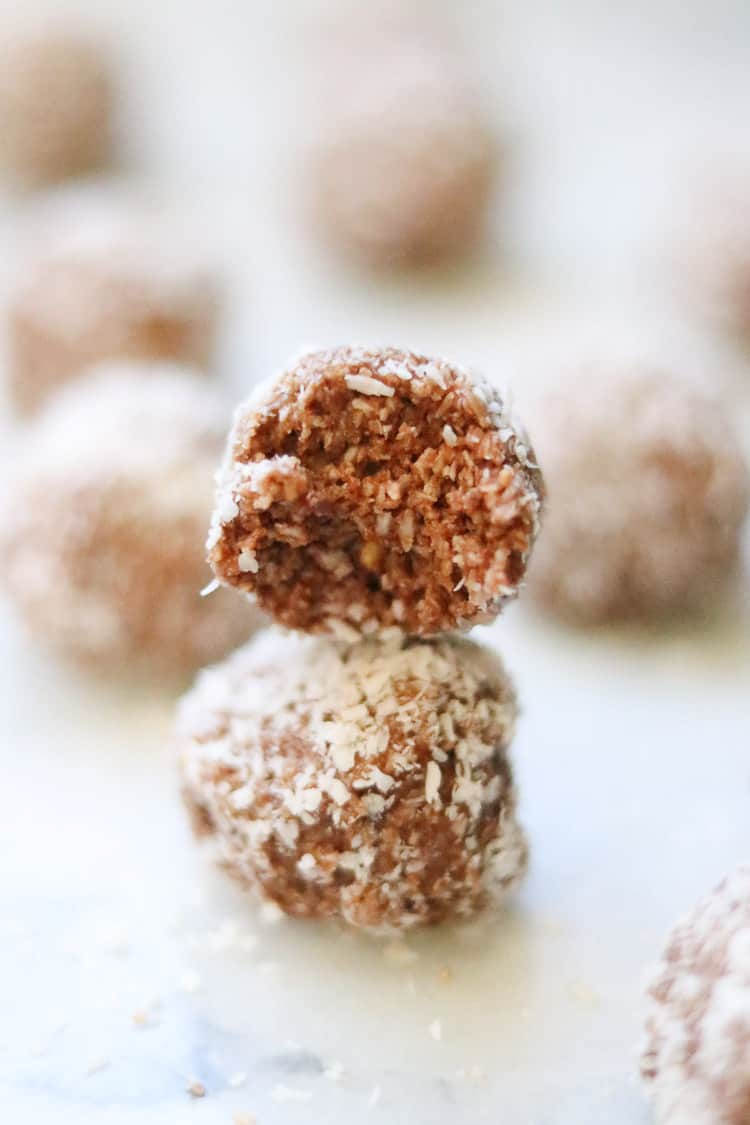 side closeup shot of vegan coconut balls stacked with a bite taken out of one