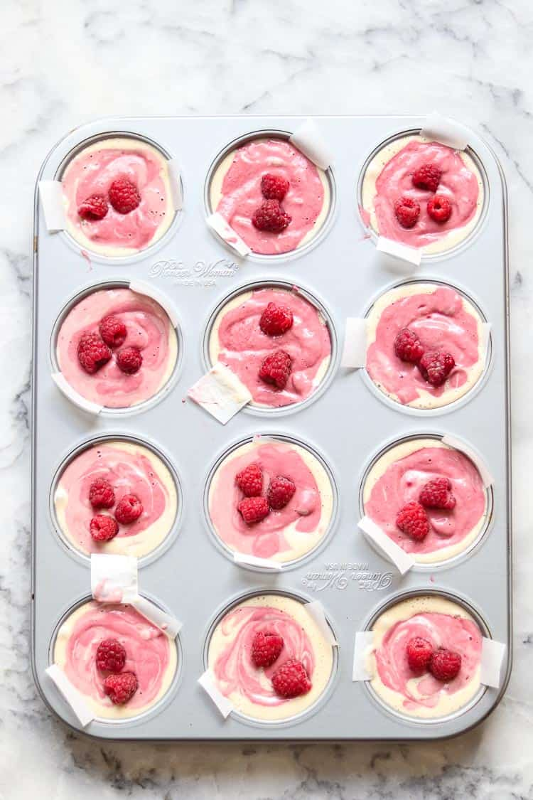overhead photo of muffin tin filled with vegan ice cream topped with raspberries on white marble background