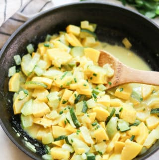 side overhead shot of vegan yellow and zucchini squash in a black skillet