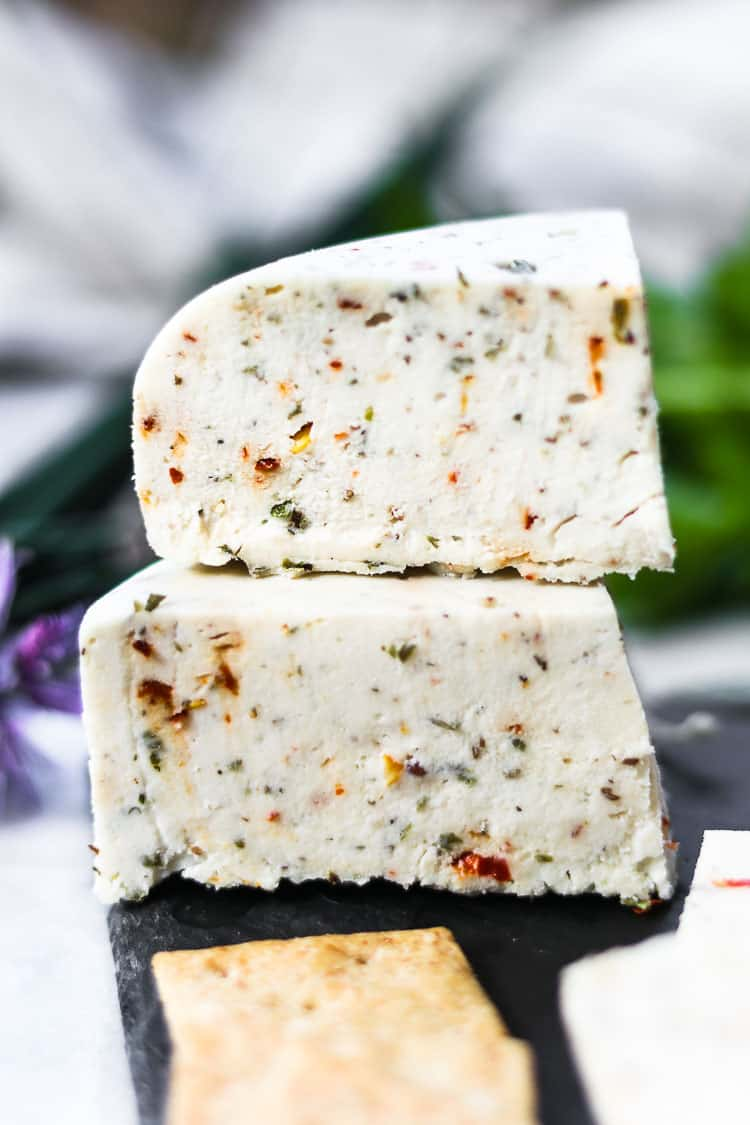 side closeup of chunks of vegan cheese with herbs showing detail and texture of cheese