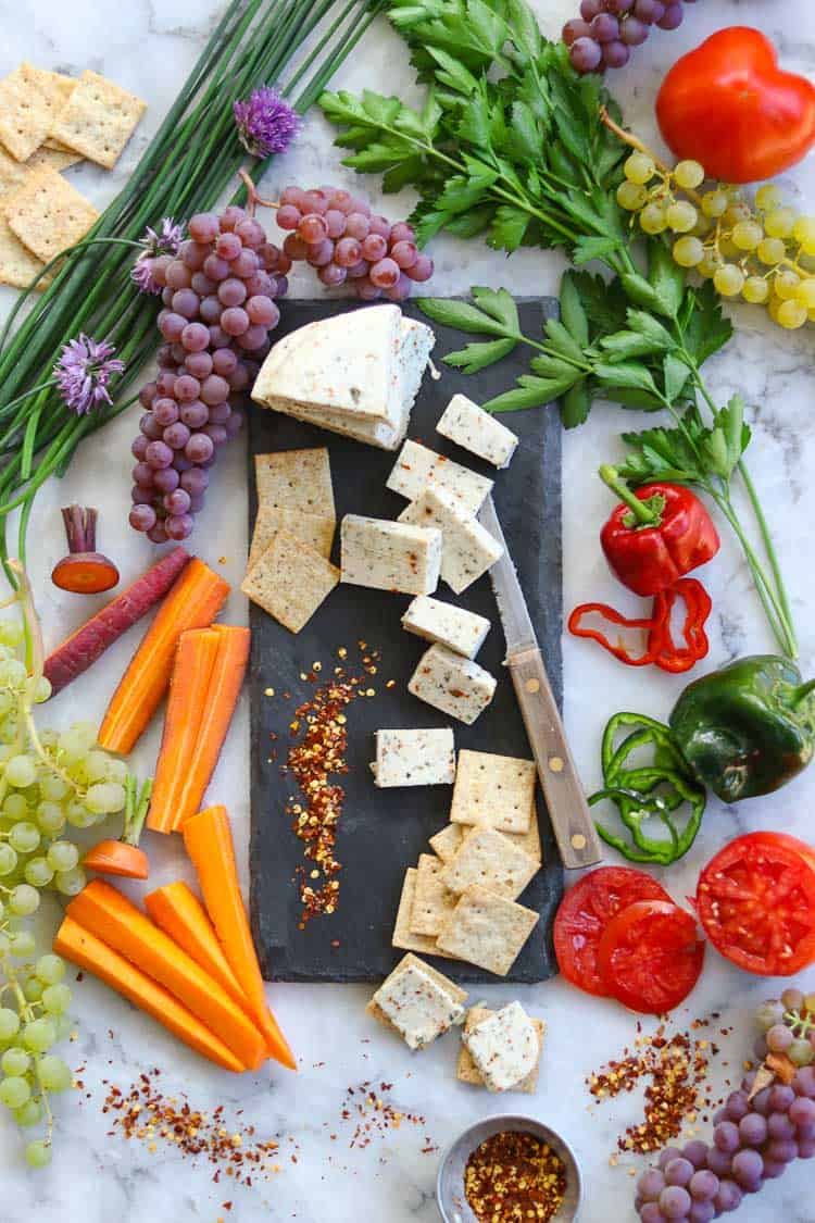 overhead shot of vegan cheese on a slate board surrounded by a variety of sliced veggies, grapes, herbs and crackers