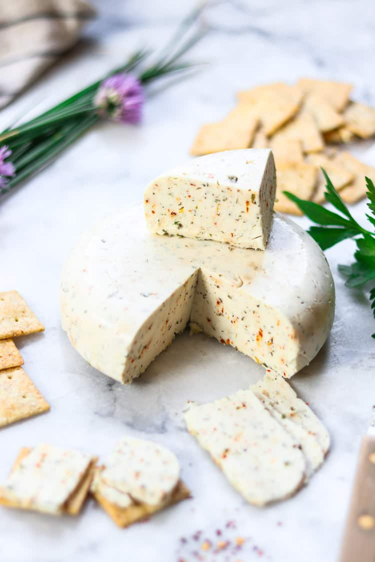 side overhead shot of vegan cheese wheel with a chunk and some slices cut out and placed on crackers