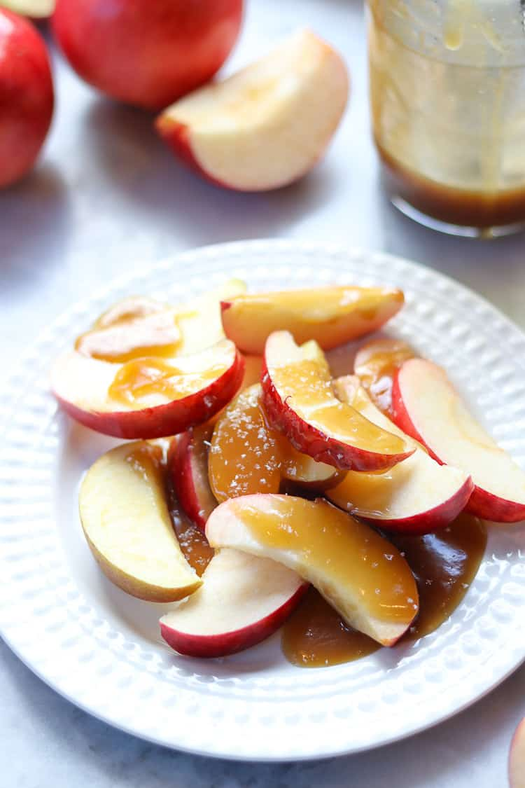 overhead closeup shot of sliced apples on white plate with caramel drizzled over and sea salt flakes sprinkled on it