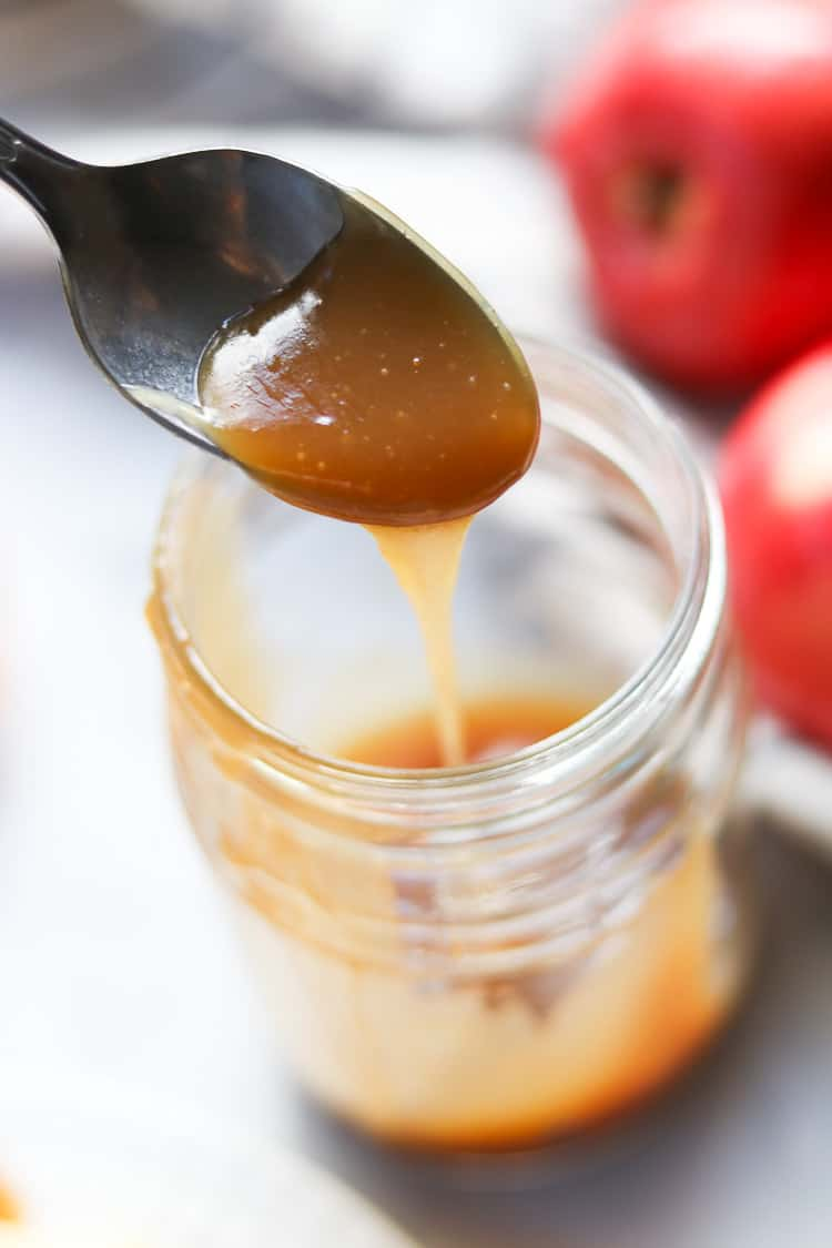 side overhead shot of silver spoon pouring vegan caramel into mason jar with apples behind