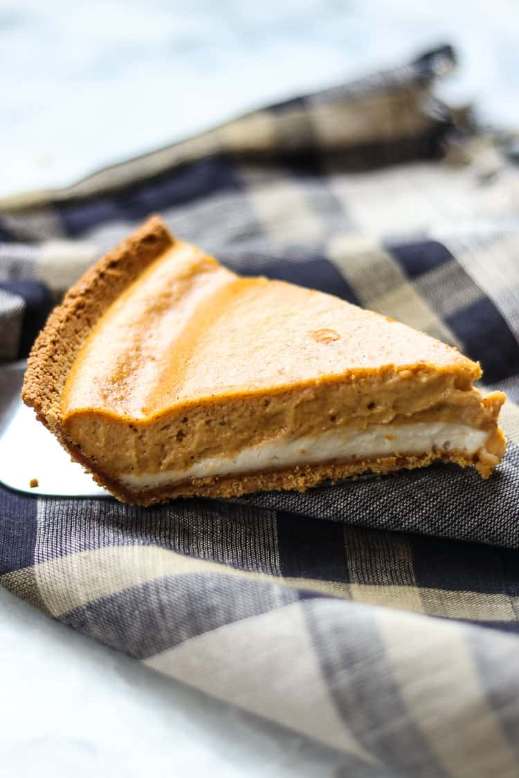 side shot of vegan double layer pumpkin cheesecake on a silver server over a plaid napkin