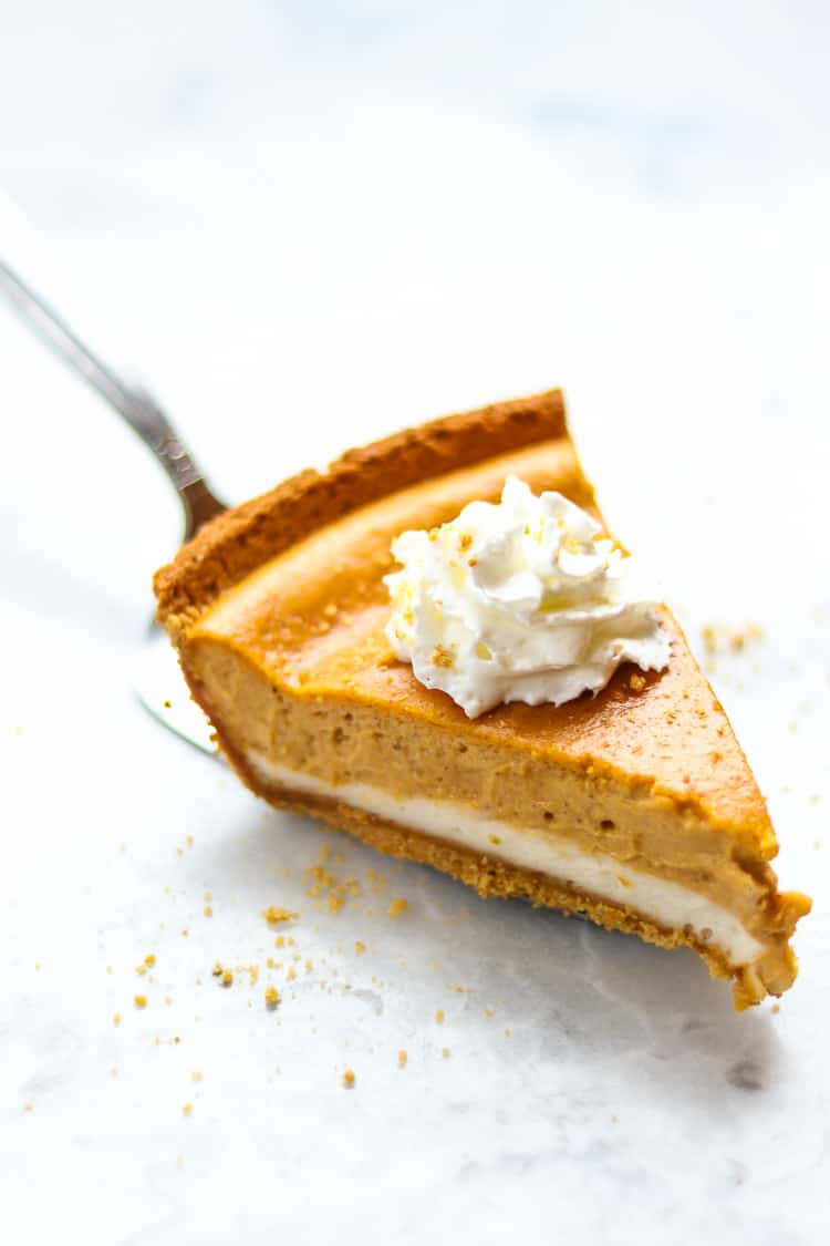 side overhead view of a slice of vegan pumpkin cheesecake on a marble background