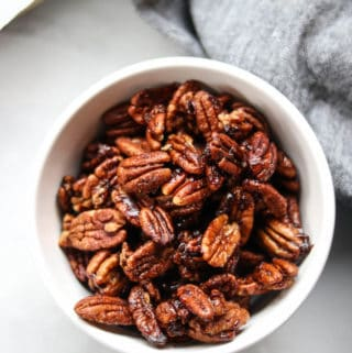 overhead shot of vegan candied pecans in a white bowl with a gray napkin and baking tray nearby