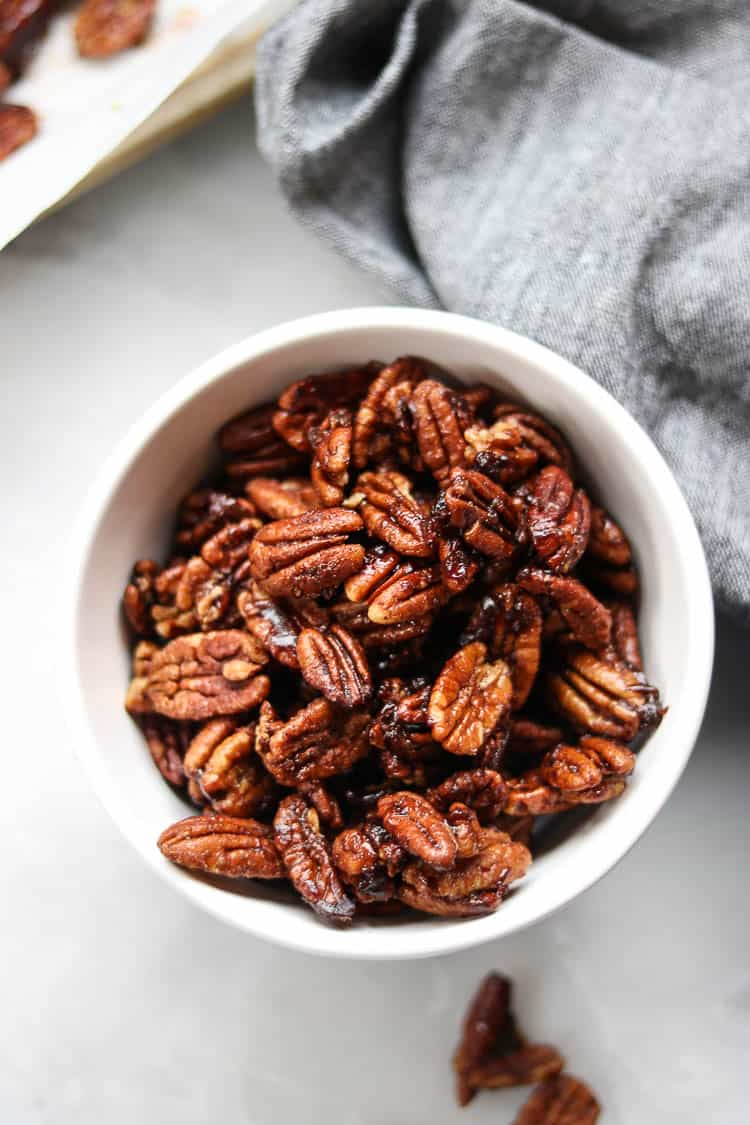 overhead closeup shot of vegan candied pecans in a white bowl with marble background