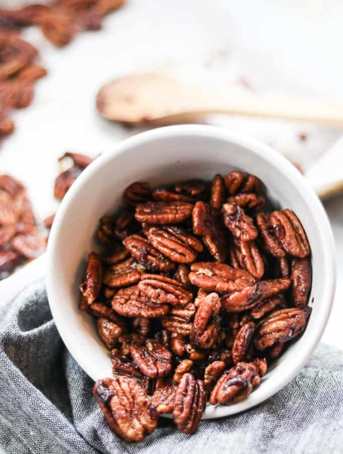 side view of white bowl of candied pecans turned on its side and spilling out