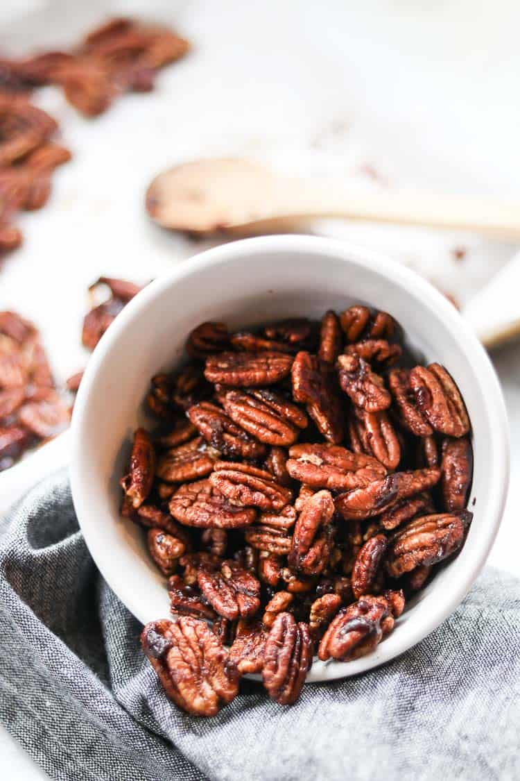 side view of white bowl of candied pecans pouring out on a gray napkin