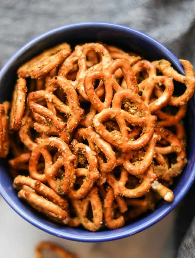 overhead closeup showing seasoned pretzels piled in a bright blue bowl