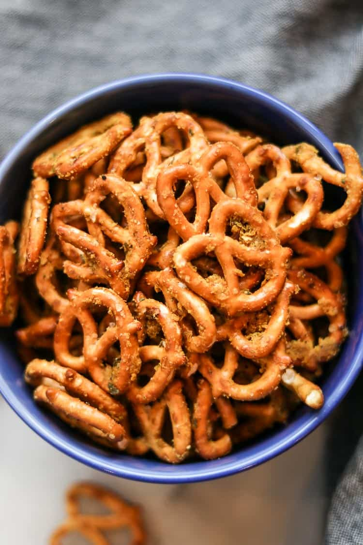 overhead closeup shot of seasoned pretzels filling a bright blue bowl