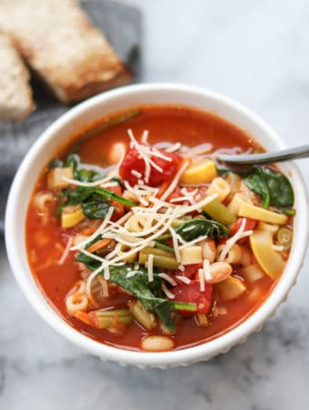 overhead photo of vegan minestrone in a white bowl with a sprinkle of vegan parmesan on top