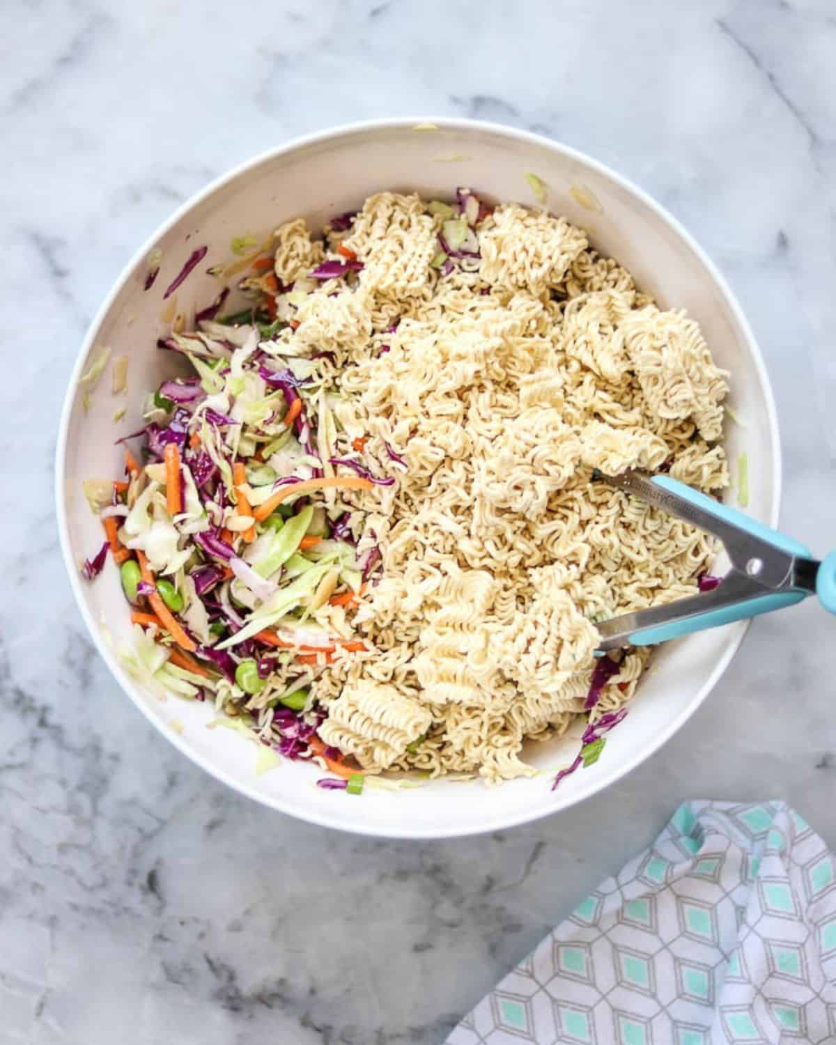 Crunchy ramen noodles and cabbage salad ingredients in a bowl.