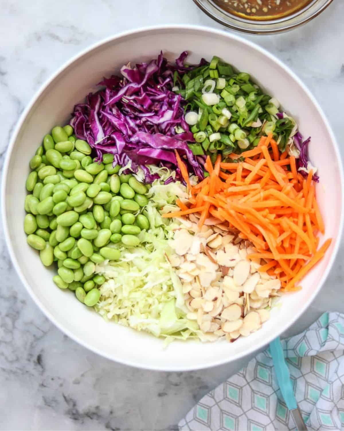Ingredients for cabbage ramen salad in a bowl.