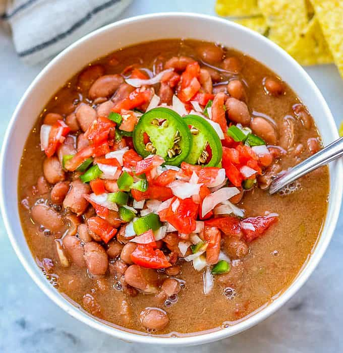 bowl of slow cooker pinto beans topped with salsa and sliced jalapenos