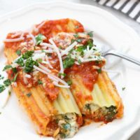 side overhead photo of two vegan manicotti shells on a white plate