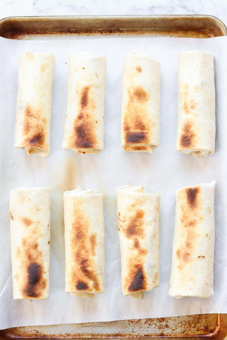 overhead photo of 8 lightly browned baked burritos lined up on a baking sheet