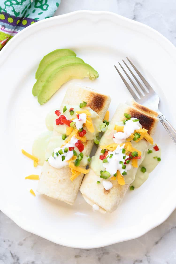 overhead photo of two chimichangas on a white plate with fork and slices of avocado beside