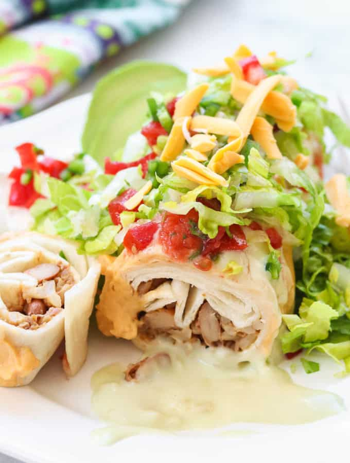 side overhead photo of sliced chimichanga on a white plate loaded with toppings including shredded cheese, lettuce, avocado, nacho cheese sauce, pico de gallo