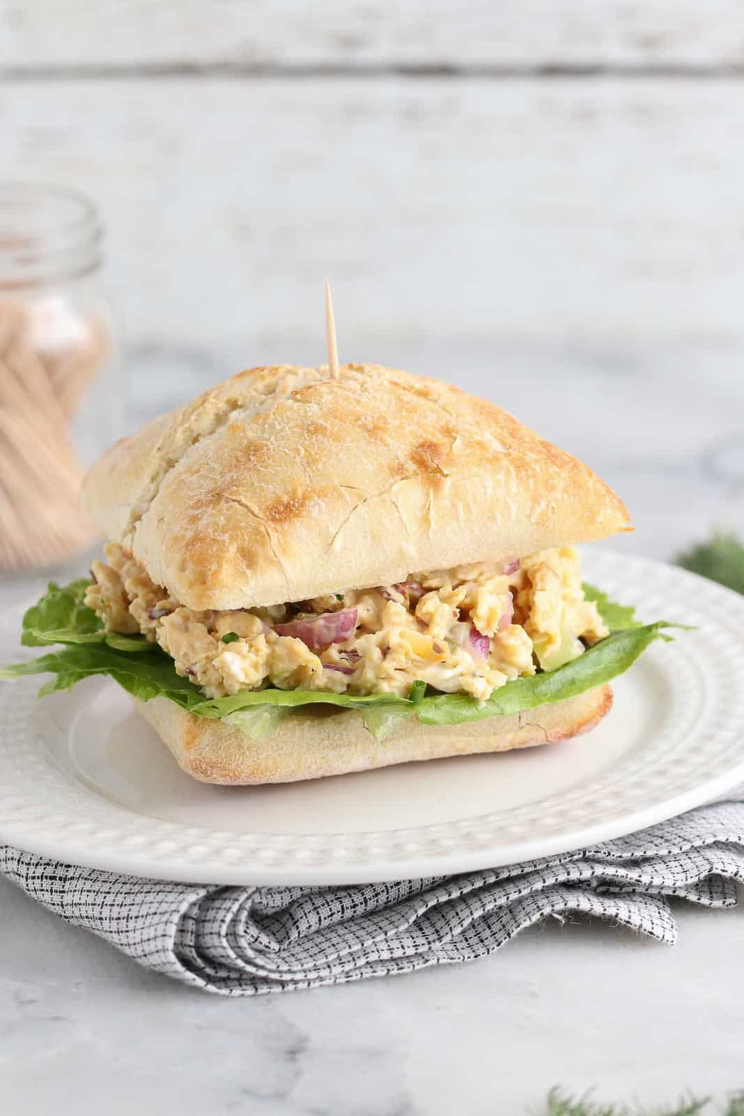 side shot of finished vegan chicken salad in a square roll on a white plate with a toothpick inserted and more in the background