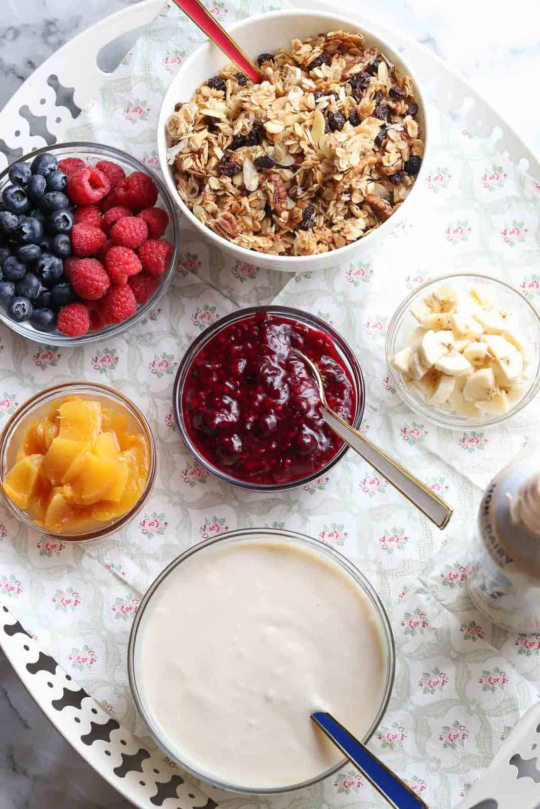wide overhead photo of fruit, granola, and whipped cream on a tray