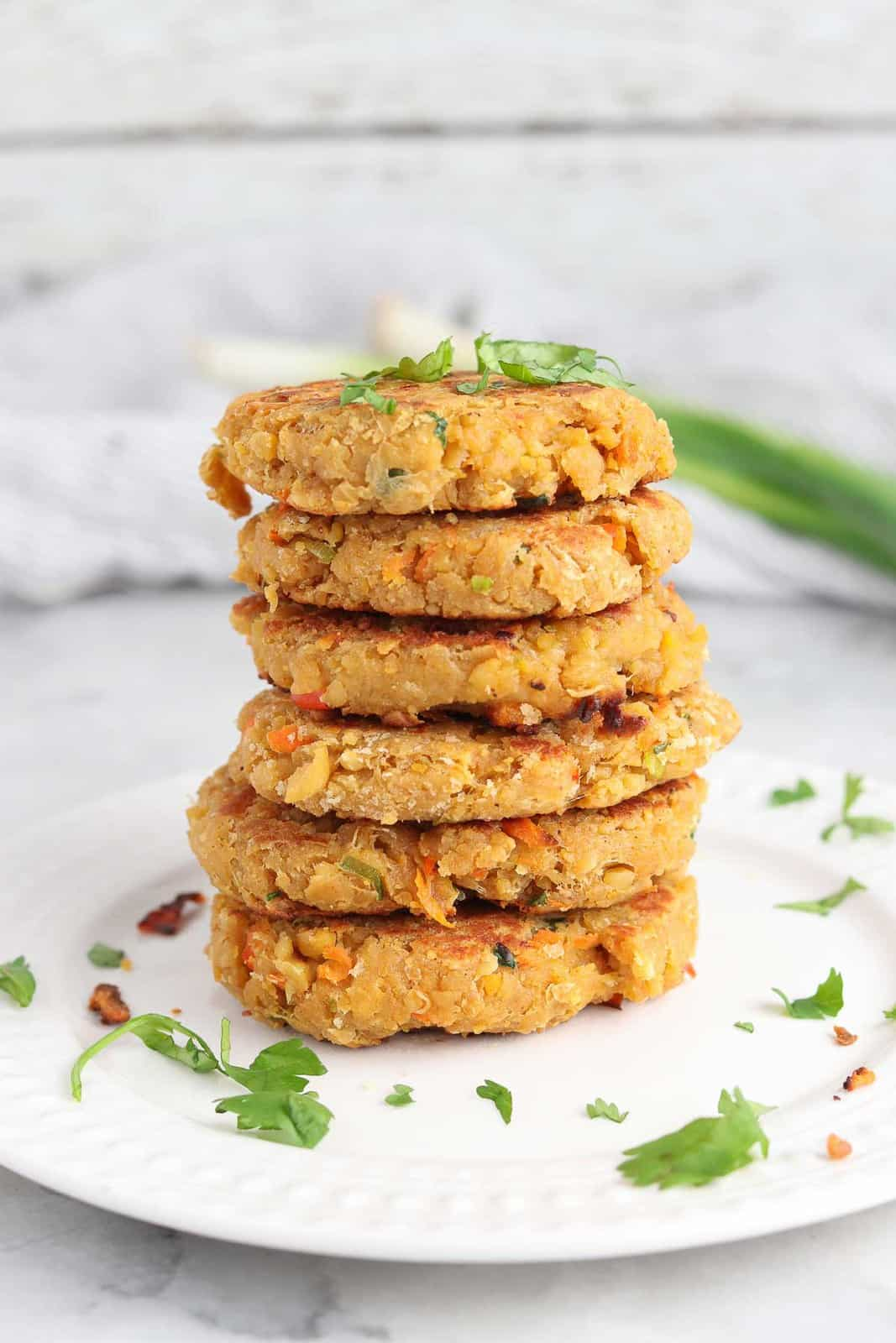 stack of vegan chickpea patties on a plate with herbs