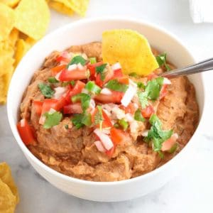 overhead view of white bowl filled with refried bean dip and topped with pico salsa with corn chips beside