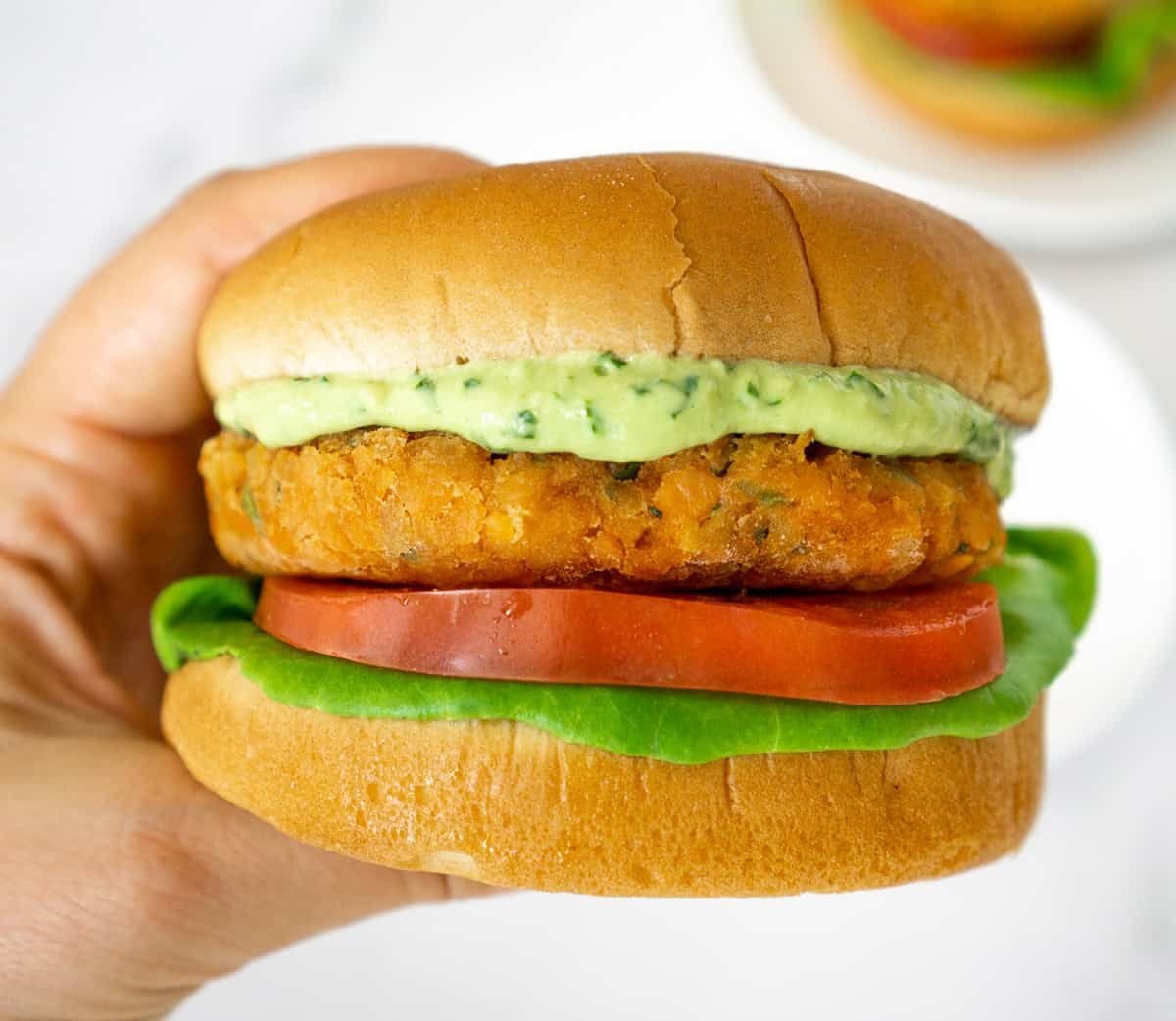 hand holding lentil burger topped with creamy vegan avocado sauce