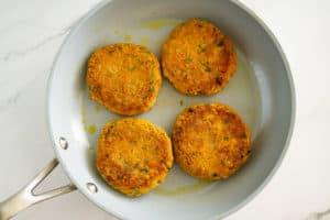 vegan lentil patties frying in a skillet