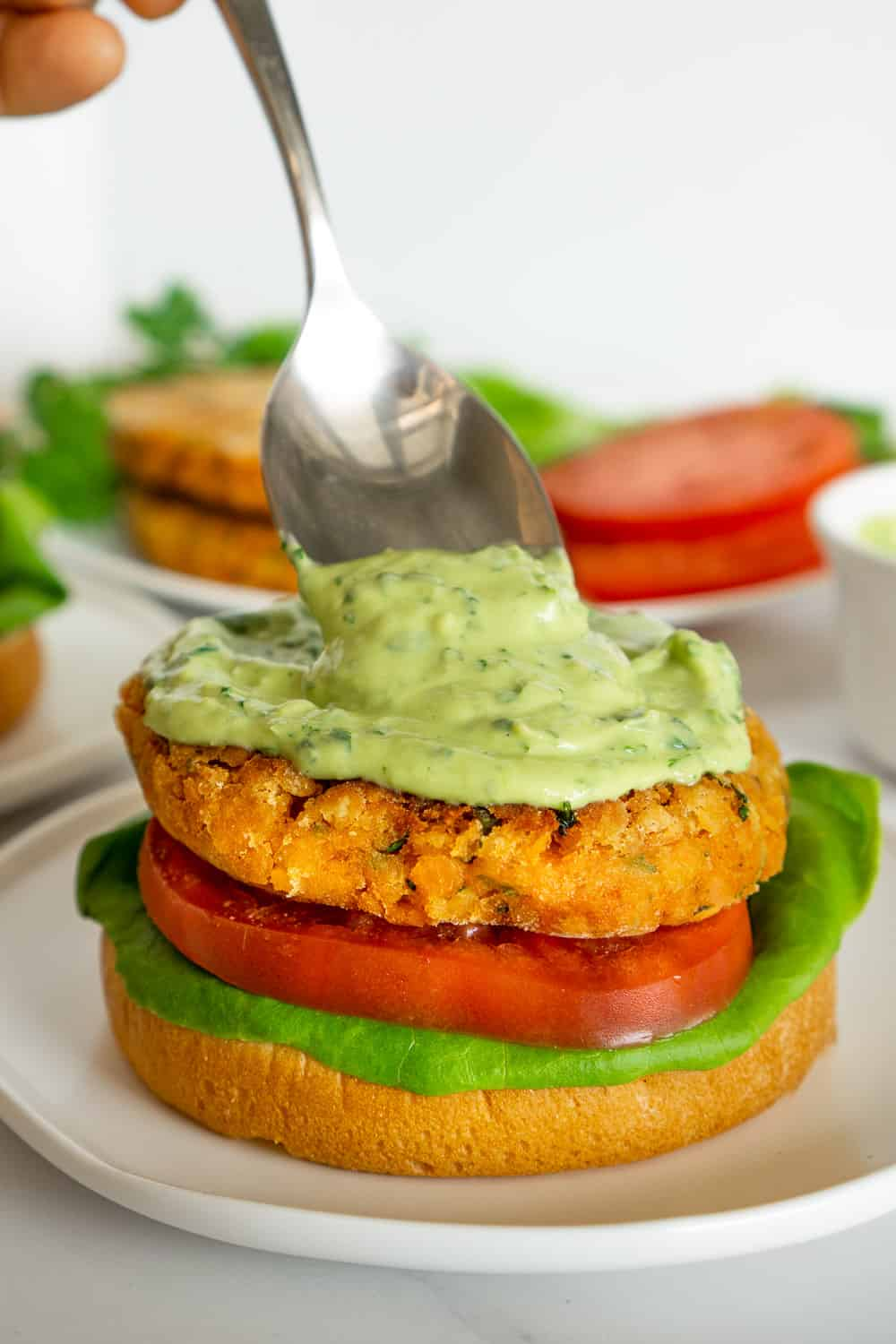 spooning avocado sauce onto lentil burgers
