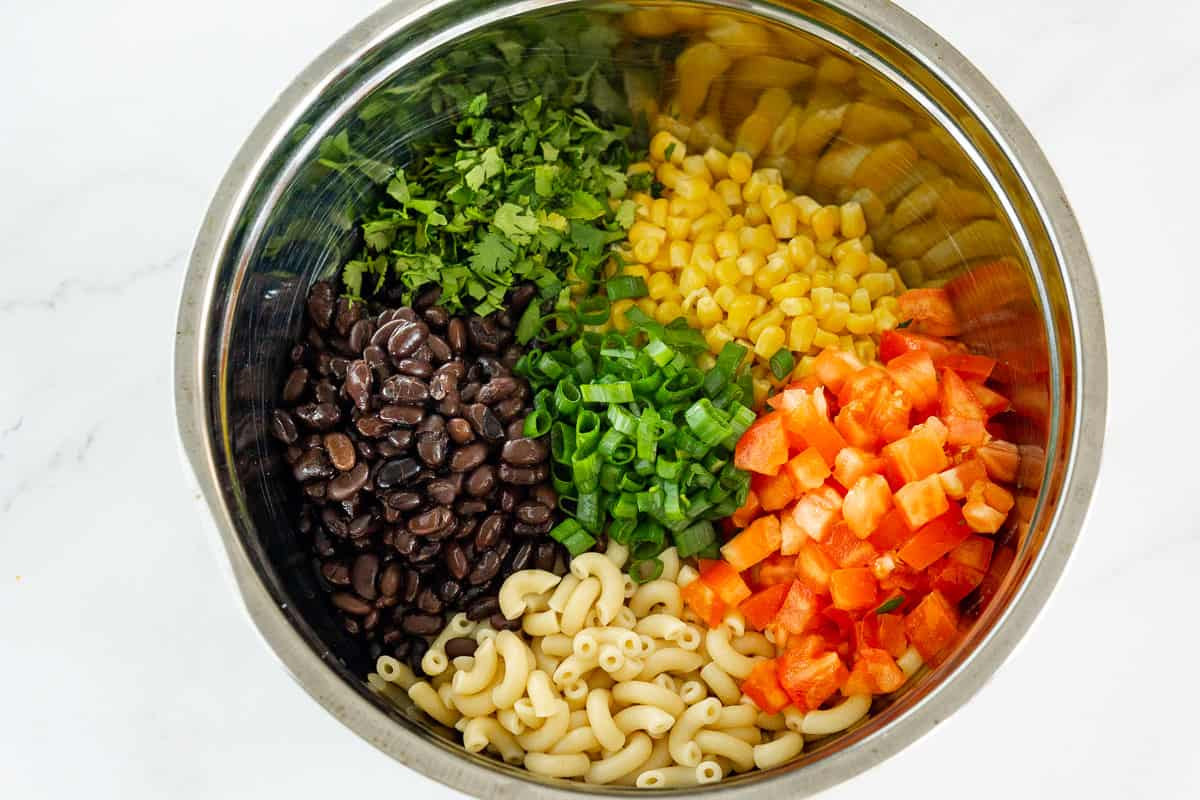 large bowl with ingredients to make a mexican macaroni salad: cooked macaroni, black beans, corn, diced tomato, cilantro, scallions