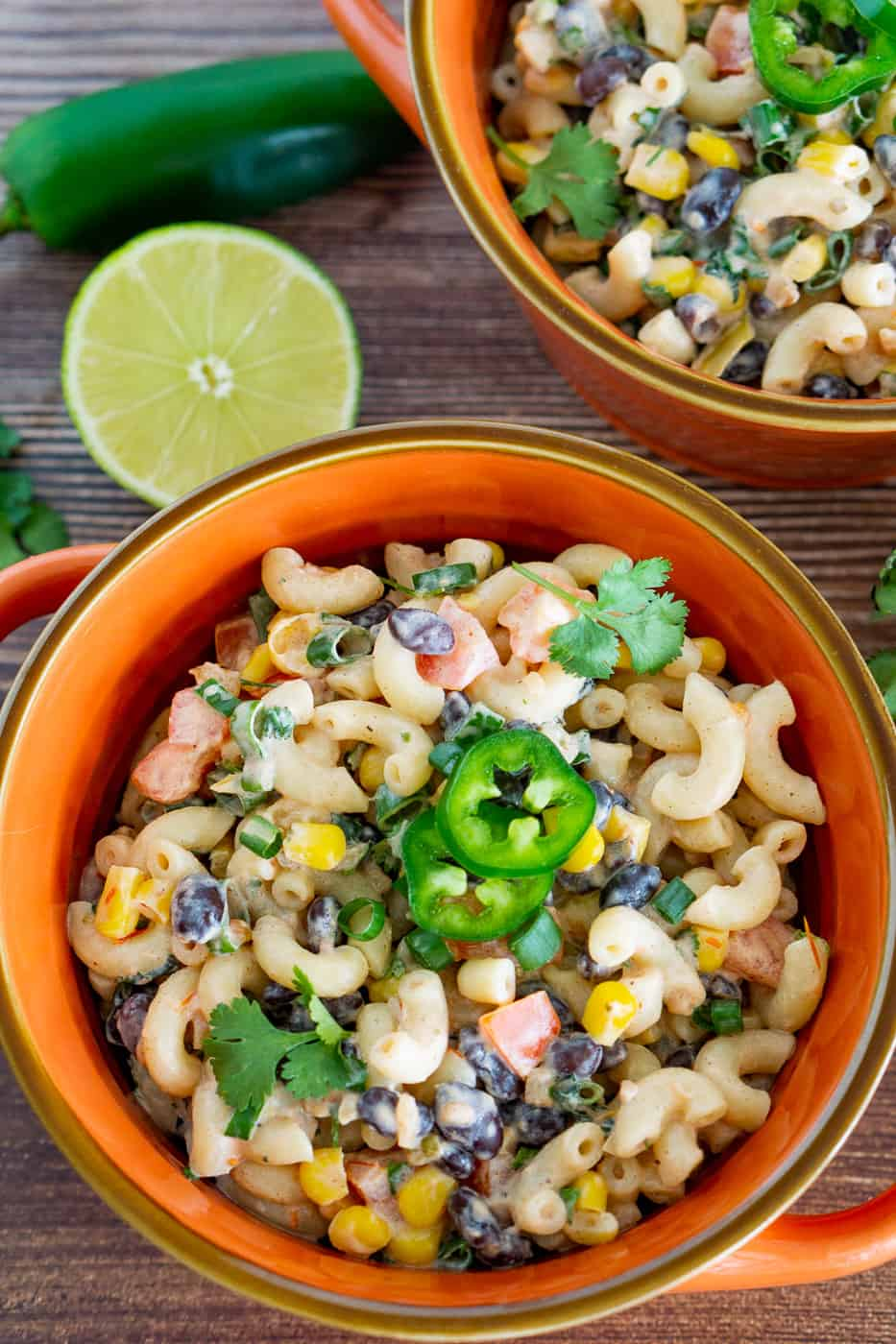 Mexican Pasta Salad with vegan creamy dressing. black beans, corn, tomatoes in a bowl topped with jalapeno garnish