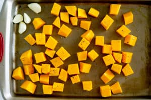cubed butternut squash and garlic cloves on a baking sheet