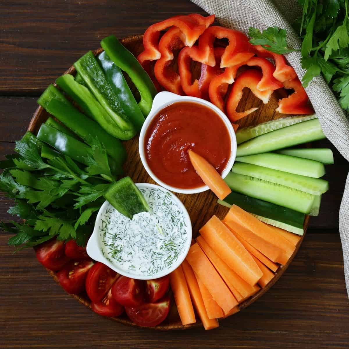 vegan appetizer plate with cut veggies, tzatziki, and red sauce