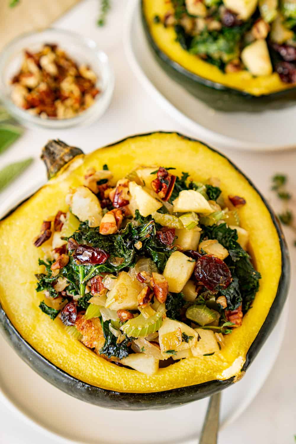 vegan stuffed acorn squash on a plate surrounded by fresh herbs and garnish