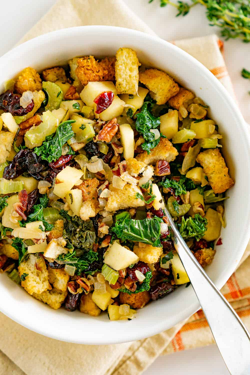 vegan stuffing in a white bowl with a spoon