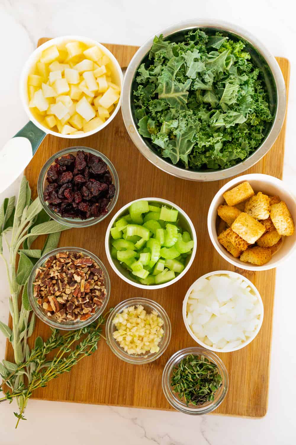 ingredients for vegan stuffing on a cutting board: apple, kale, celery, onion, croutons, garlic, pecans, dried cranberries, and fresh sage and thyme