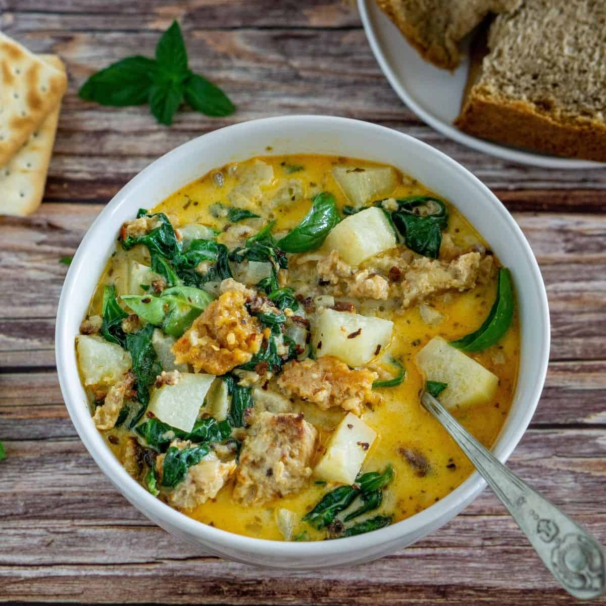 vegan zuppa toscana in a while bowl with crackers and bread on the side