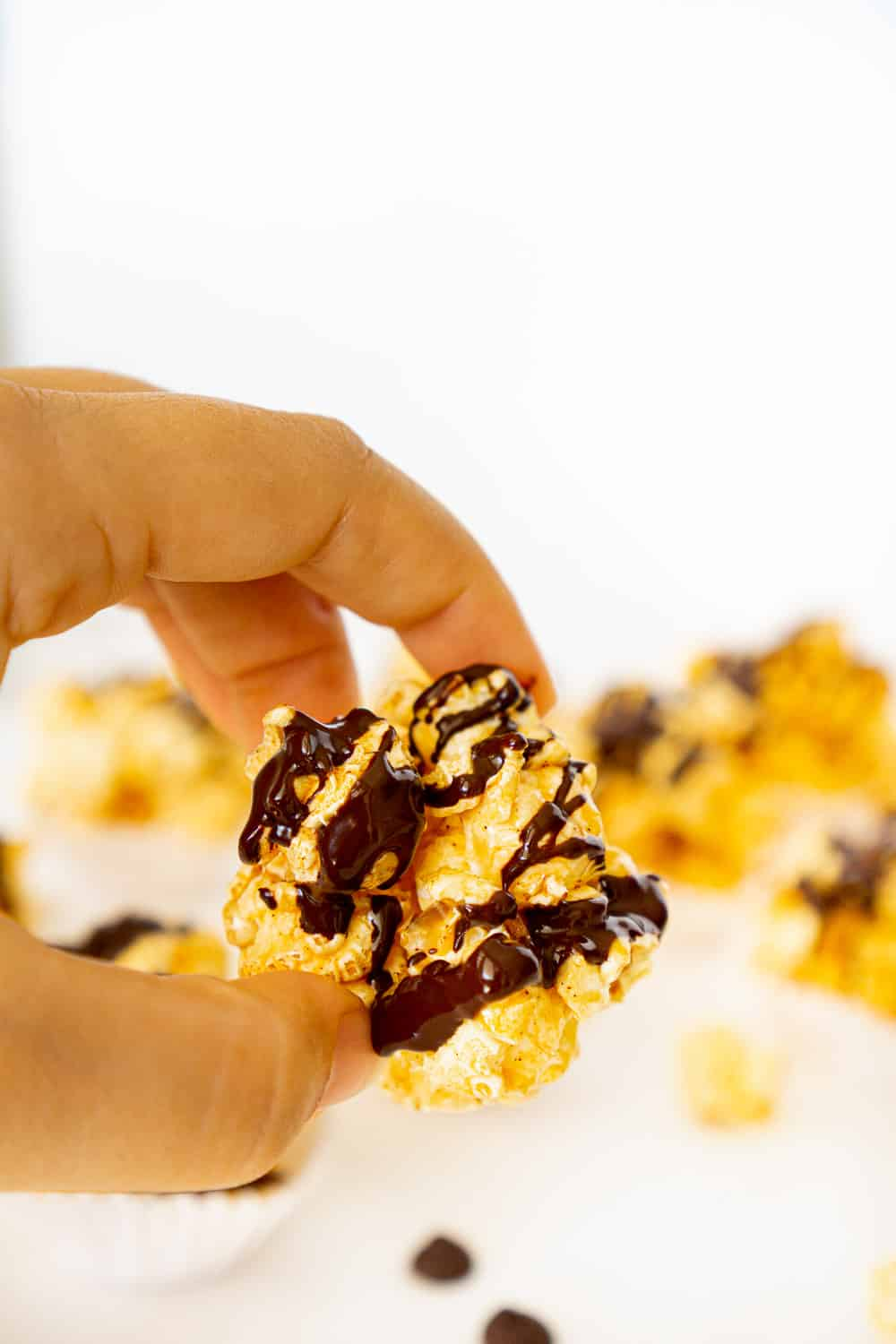 hand holding chocolate covered popcorn ball