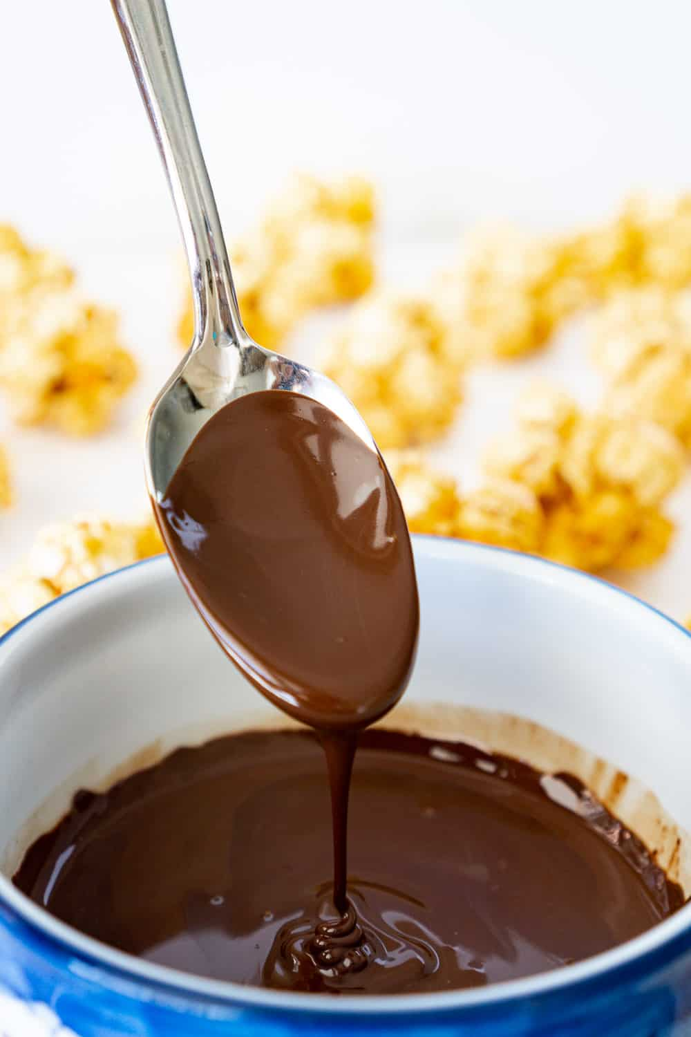 bowl of melted dark chocolate with a spoon, with popcorn balls in the background