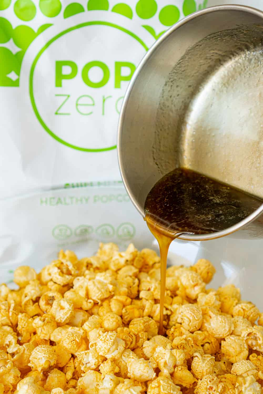 pouring maple caramel into a bowl of popcorn