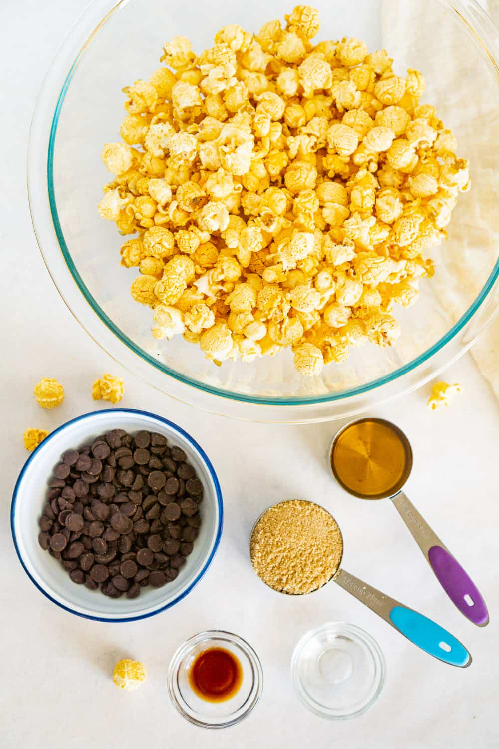 ingredients to make vegan chocolate popcorn balls: popcorn, dark chocolate, maple syrup, brown sugar, vanilla