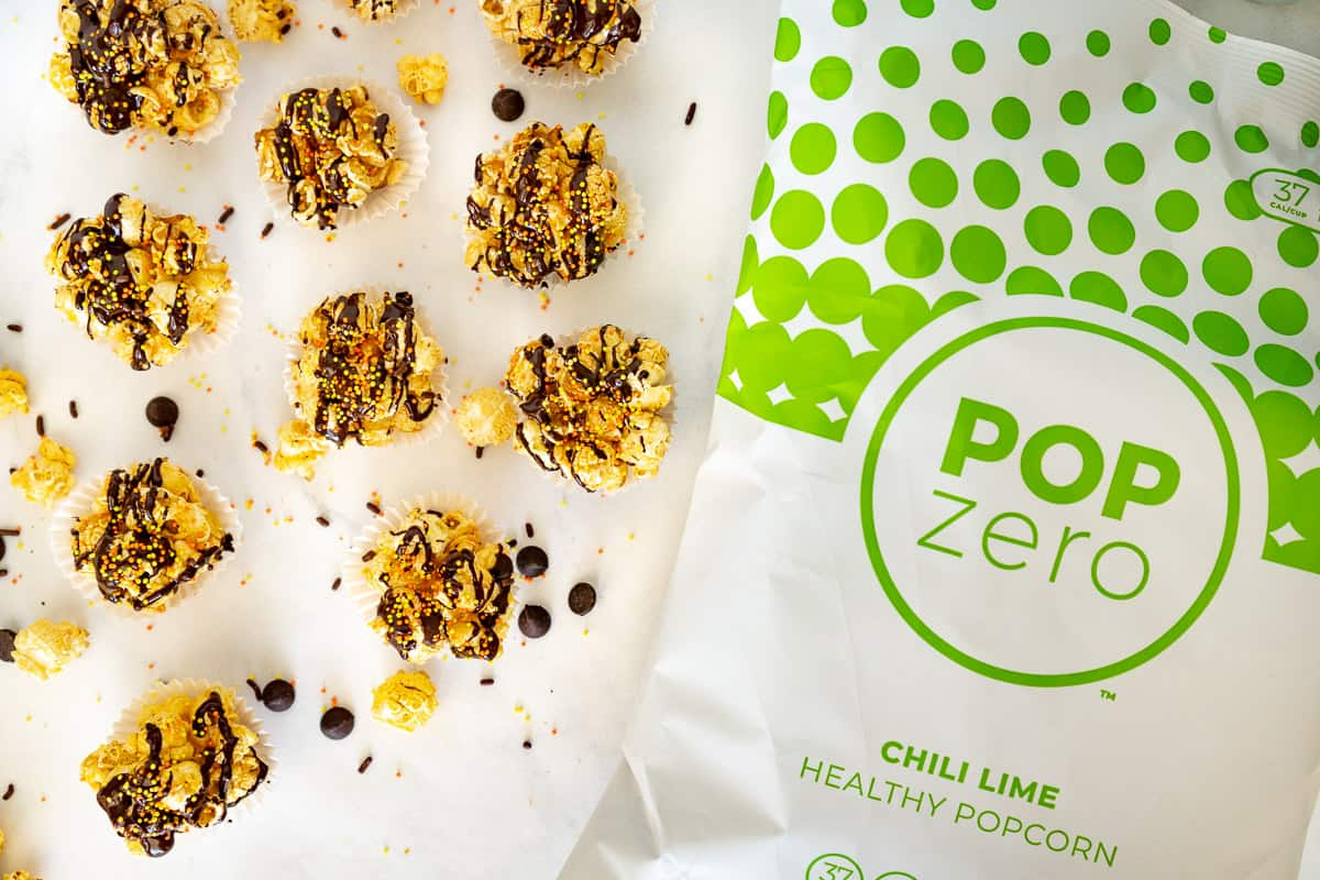bag of popzero popcorn next to chocolate popcorn balls