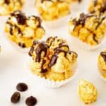 close up of chocolate popcorn ball in a muffin liner with chocolate chips on the side